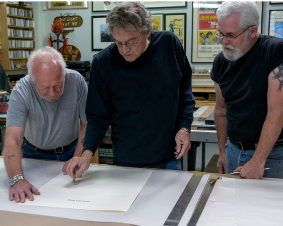 "Allen at Landfall Press in Santa Fe, reviewing the art prints for his new album. ""I had the sheet music blown up and I'm using those as the element that I'm drawing on and altering. I just shot a hole through one of them, for 'Queenie's Song.'"" (Photo by Peter Ellzey)"