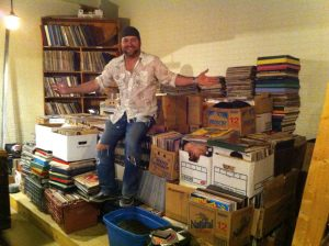 Superfly's Lone Star Music Emporium owner Zach Jennings atop just one of his piles of vinyl.