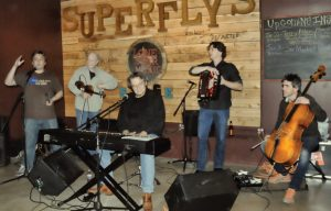 Top of the World: Editor Richard Skanse (left), introducing Terry Allen (at keyboard) and his band (Richard Bowden on fiddle, Bukka Allen on accordion, and Brian Standefer on cello) at Superfly's Lone Star Music Emporium in San Marcos on Jan. 22, 2013. (Photo by Diana Hendricks)