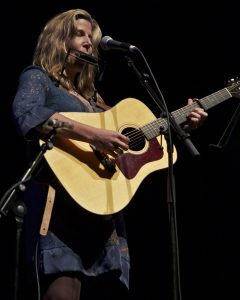 """Terri Hendrix performing """"The Dark"""" at Guy Clark's 70th Birthday tribute at Austin's The Long Center for Performing Arts. (Photo by Machelle Dunlop)"""