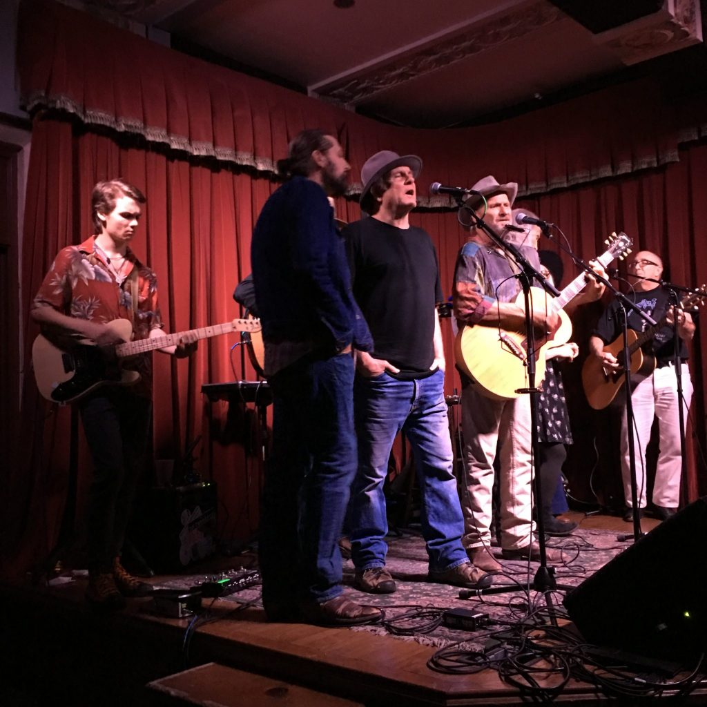"For the Sake of the Songs: (from left) Rory Hancock, Graham Weber, Derral Gleason, Butch Hancock, Jimmie Dale Gilmore, BettySoo, and Mickey White closing the 19th annual Townes Van Zandt birthday salute at the Cactus Cafe with ""Pancho & Lefty."" (Photo by Susan Cane)"