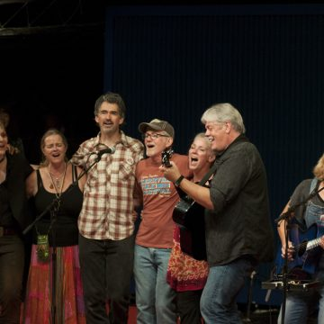 "This One's For Rod: Texas songwriter Terri Hendrix and Lloyd Maines performing ""Hole in My Pocket"" with Kerrville friends and fellow Rod Kennedy fans Vance Gilbert, Mary Gauthier, Cyd Cassone, Slaid Cleaves, Johnsmith, Kristin DeWitt, and Ruthie Foster. (Photo by Nichole Wagner)"