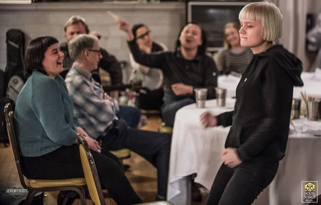 Kalyn Fay of Tulsa, Oklahoma, laughs as Rebecka Diggervall of Sweden gets down during a House of Songs Ozarks gathering. Founder Troy Campbell, conducts in the background. (Photo by Jeremy Scott)