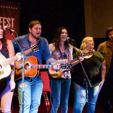 "The Brumley Bunch: Chris Hawkes, Miranda Dawn, Graham Wilkinson, Taasha Coates, Betsy Brumley, Dan Crannitch and Troy Campell, singing ""I'll Fly Away"" at AmericanaFest 2017 in Nashville. (Photo by Lynne Margolis)"