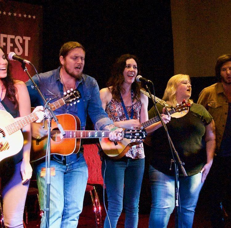 "The Brumley Bunch: Chris Hawkes, Miranda Dawn, Graham Wilkinson, Taasha Coates, Betsy Brumley, Dan Crannitch and Troy Campell, singing ""I'll Fly Away"" at AmericanaFest 2017 in Nashville. (Photo by Lynne Margolis)"