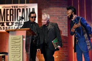 "Deja vu all over again: John Prine collecting his second consecutive ""Artist of the Year"" award from presenters Alejandro Escovedo and Fantastic Negrito. (Photo by Erika Goldring/Getty Images for Americana Music Association)"